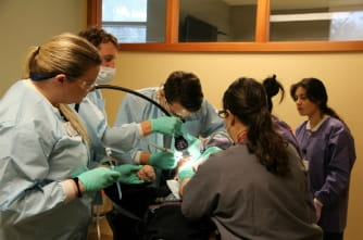 Faculty and students working with a patient in the Special Needs Clinic