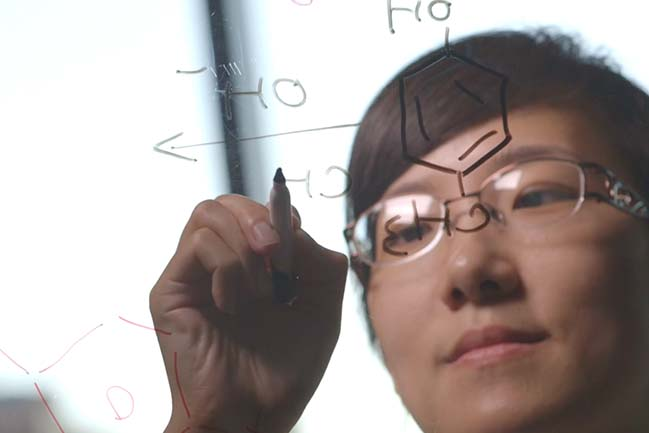 Image of scientist using a clear board to diagram molecules