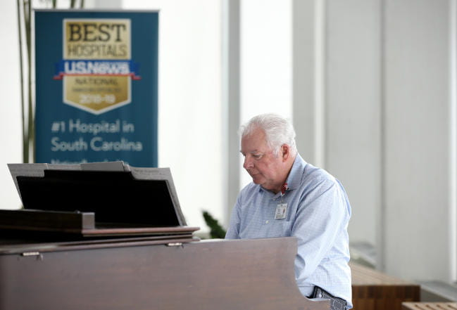 Smiling Arts in Healing volunteer musician performer playing piano for MUSC hospital community