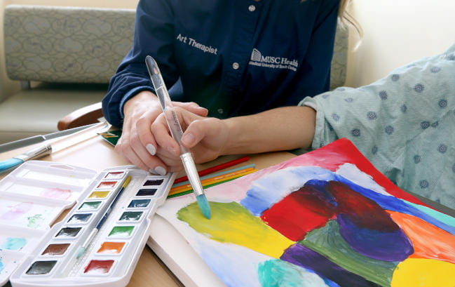 MUSC Arts in Healing art therapist with hospital patient at the bedside painting colorful images in art therapy session