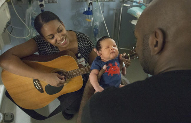Arts in Healing Music Therapist singing and providing music therapy interventions to pediatric patient, dad, and family at MUSC Children's Hospital