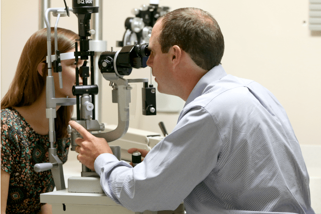 Dr. Magrath performs an eye exam on a patient.