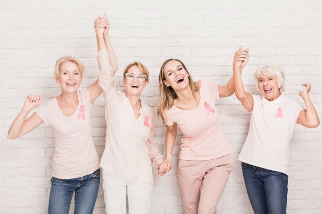 Image of four smiling women raising their arms in celebration.
