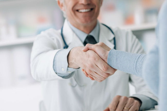 caregiver shaking patient's hand