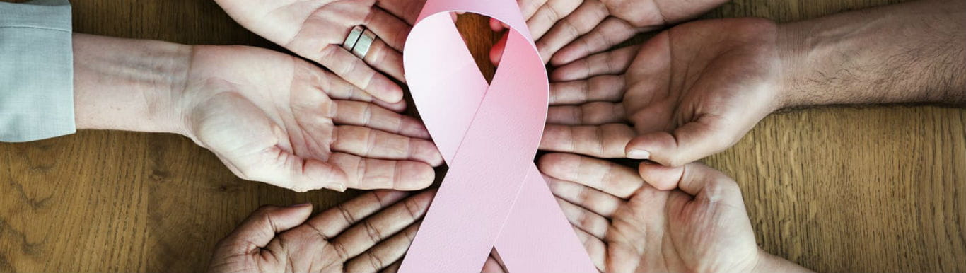 Image of hands surrounding a pink ribbon