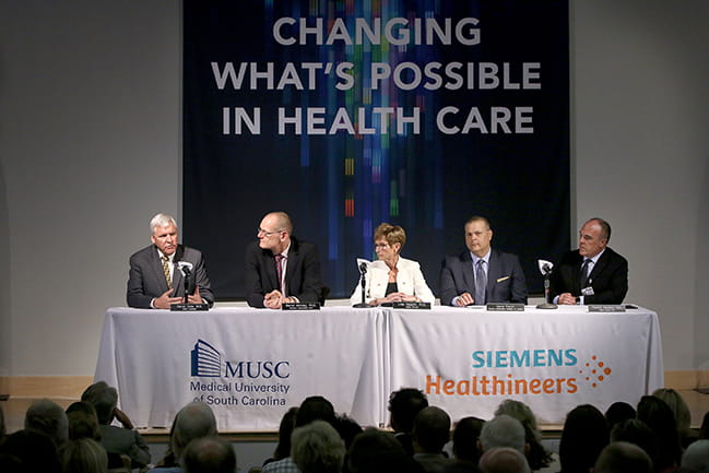 David Cole, MD, FACS, president of MUSC, is seated with Michael Saladin, PhD, & Patrick Cawley, MD, MUSC Health CEO, University Vice President of Health Affairs, as well as Siemens officials as they announce their partnership at a press conference.