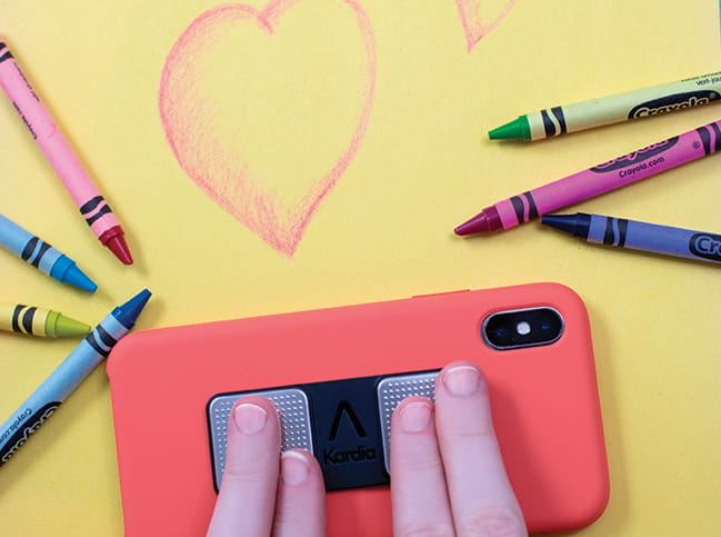 Image of a child's fingers on an electronic device surrounded by crayons scattered on a yellow background with a heart drawn on it.