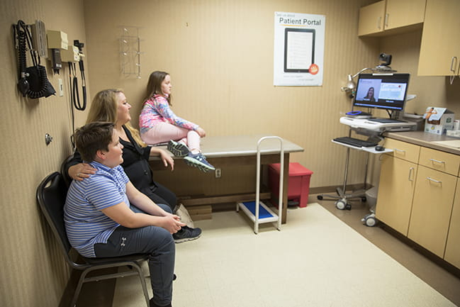 patient and family looking at provider on telemedicine cart screen