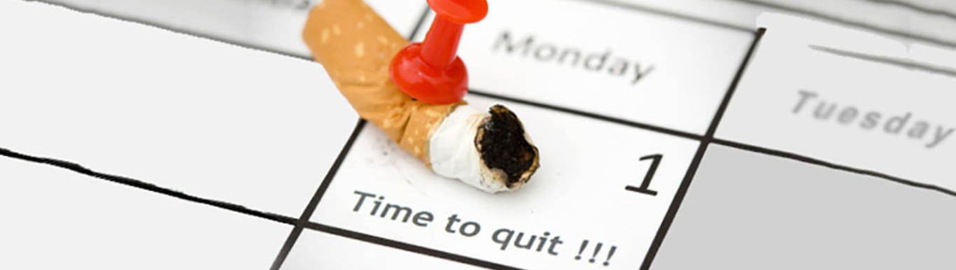 Calendar with a burnt cigarette pinned to a day that says Time to Quit.