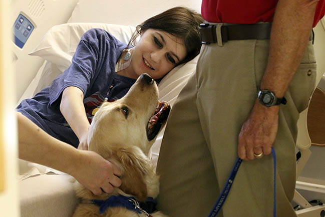 Smiling patient with pet therapy dog, Bodie