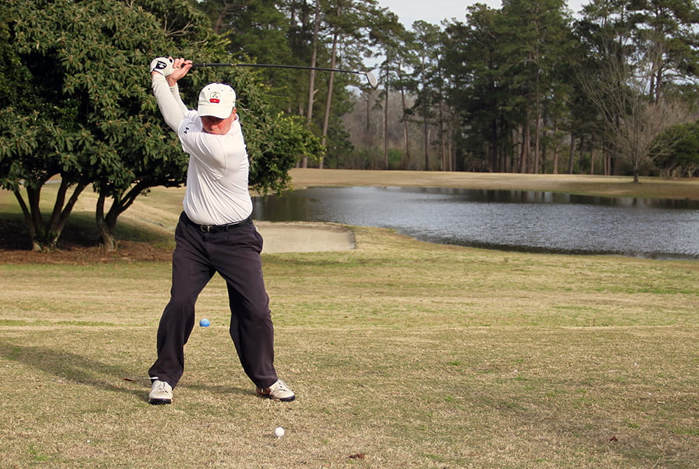 A man takes a swing at a golf ball on a golf course