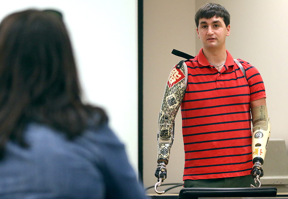 A man with two prosthetics for arms speaks in a classroom
