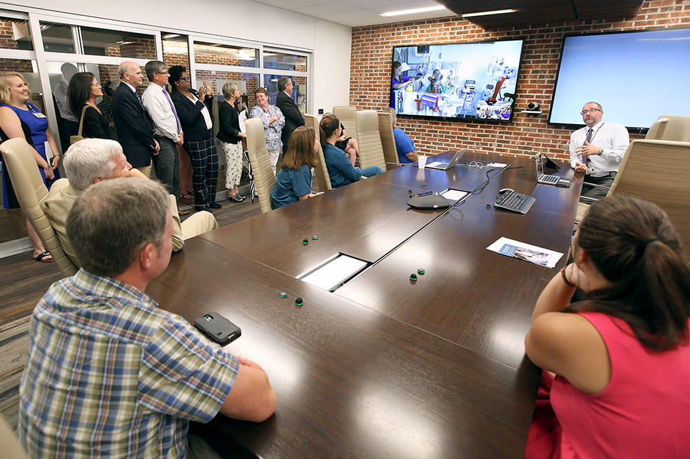 people gather around a conference room table to watch a doctor interact with a remote patient through a large video screen