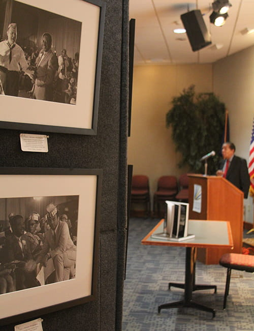 A display of old black and white photos, while in the background the photographer speaks at a podium