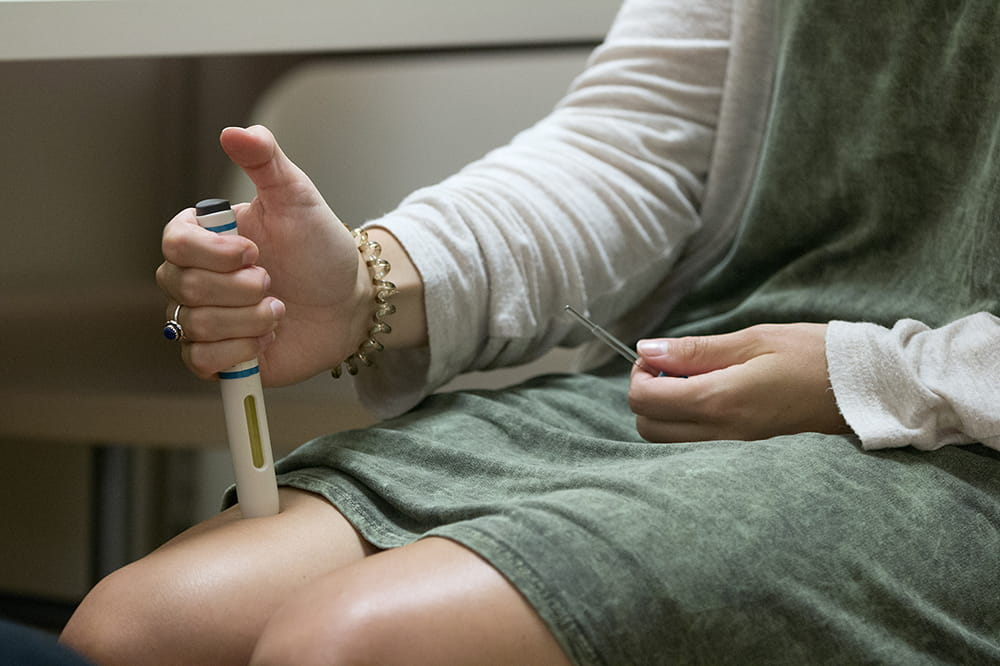 a close-up of a woman pretending to inject a medication into her leg above her knee