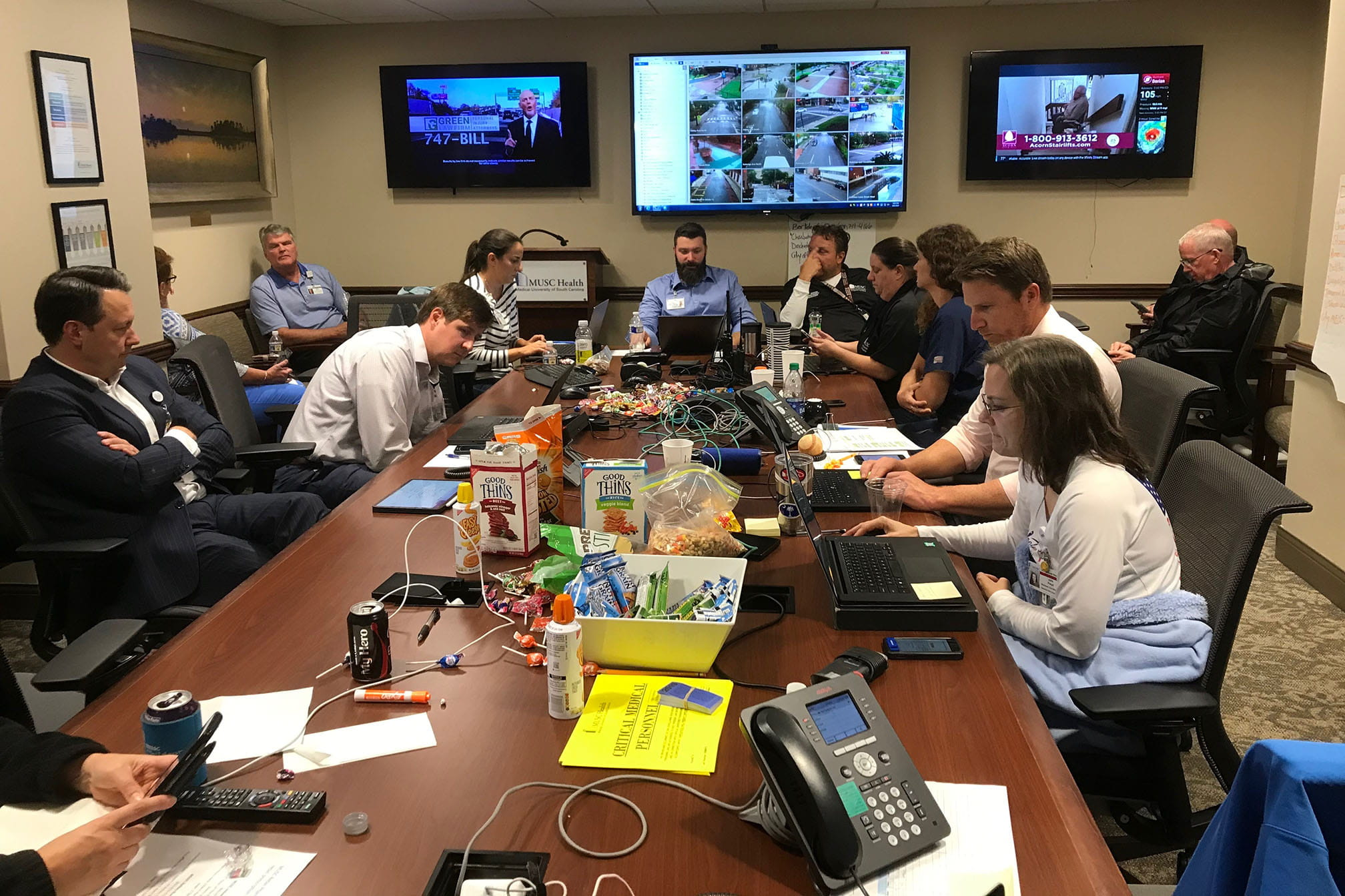 A look inside the command center at MUSC. Monitors on walls show locations across campus as people work on computers around a conference table