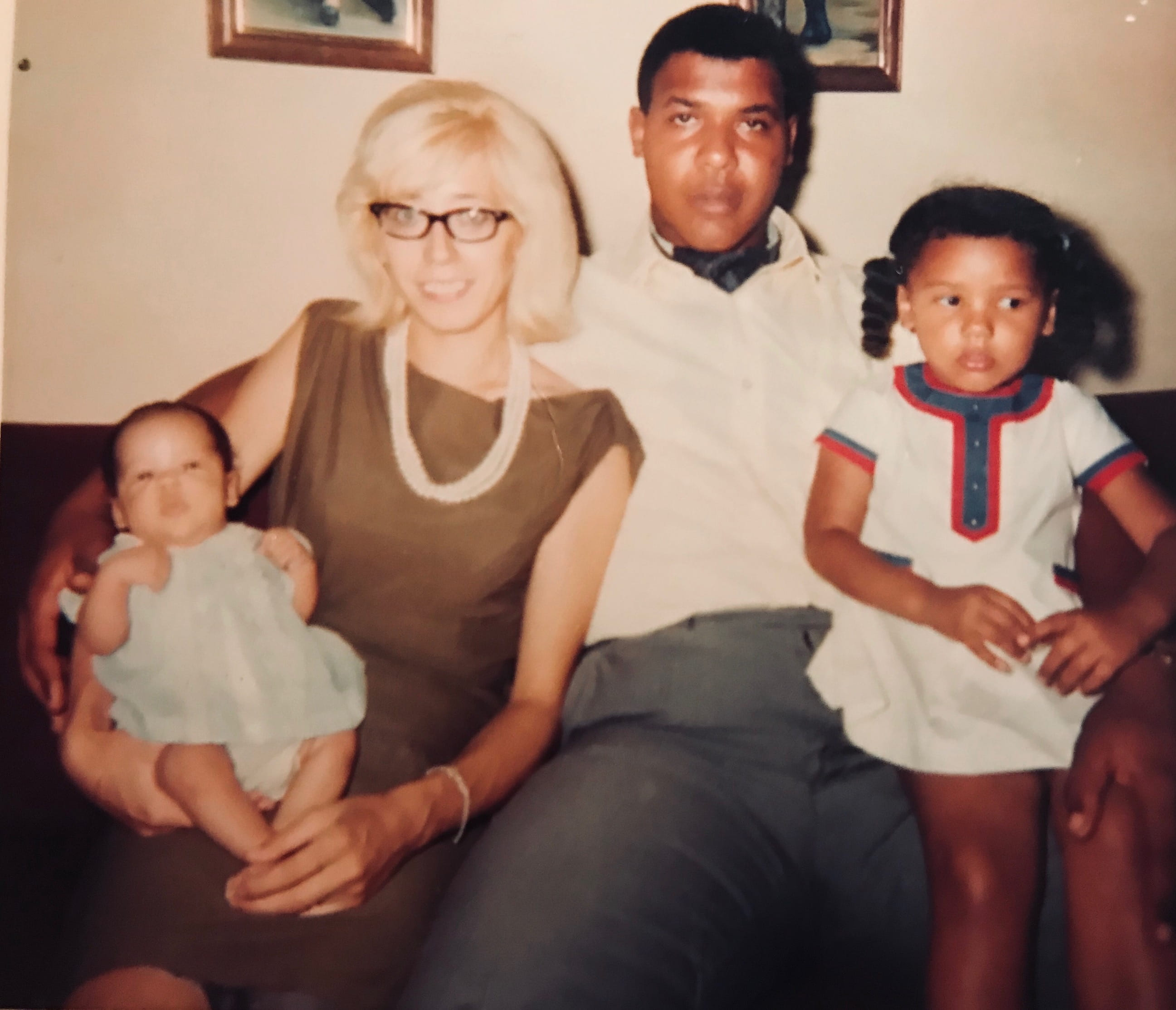old photo of family sitting on couch. there is a mom and dad and on either end is a baby and an toddler