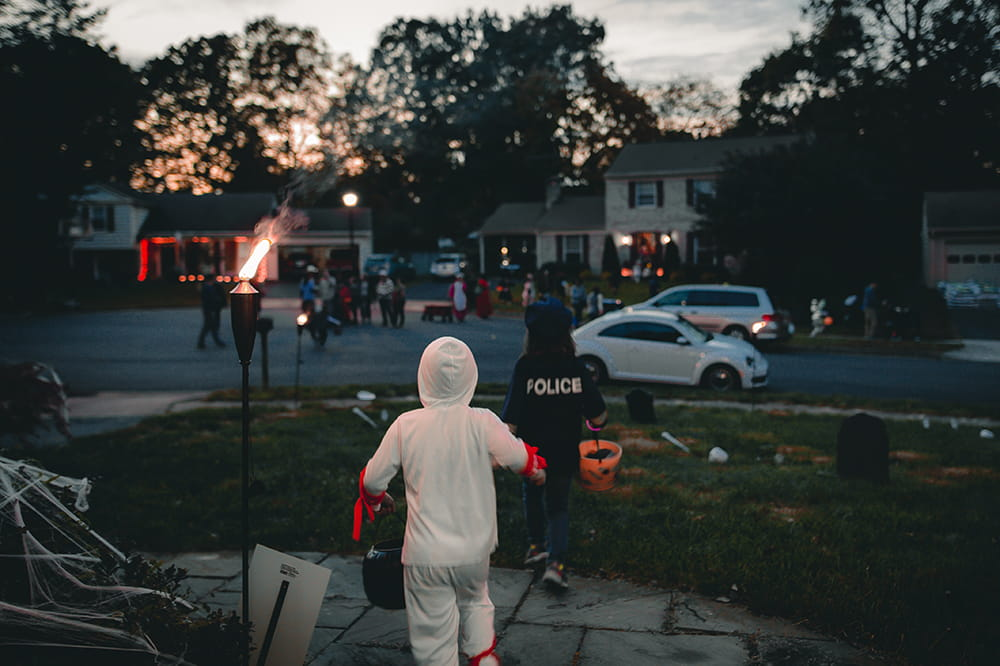 A twilight image of children in costumes running around a suburban neighborhood trick or treating