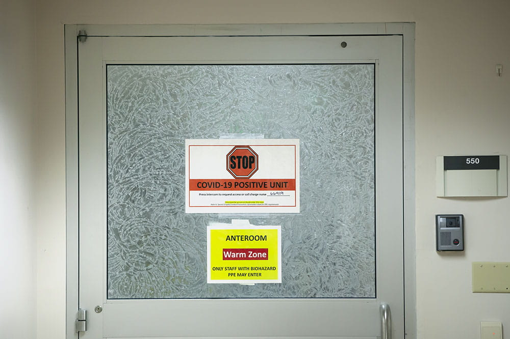Signs on a door saying it Is a COVID unit.