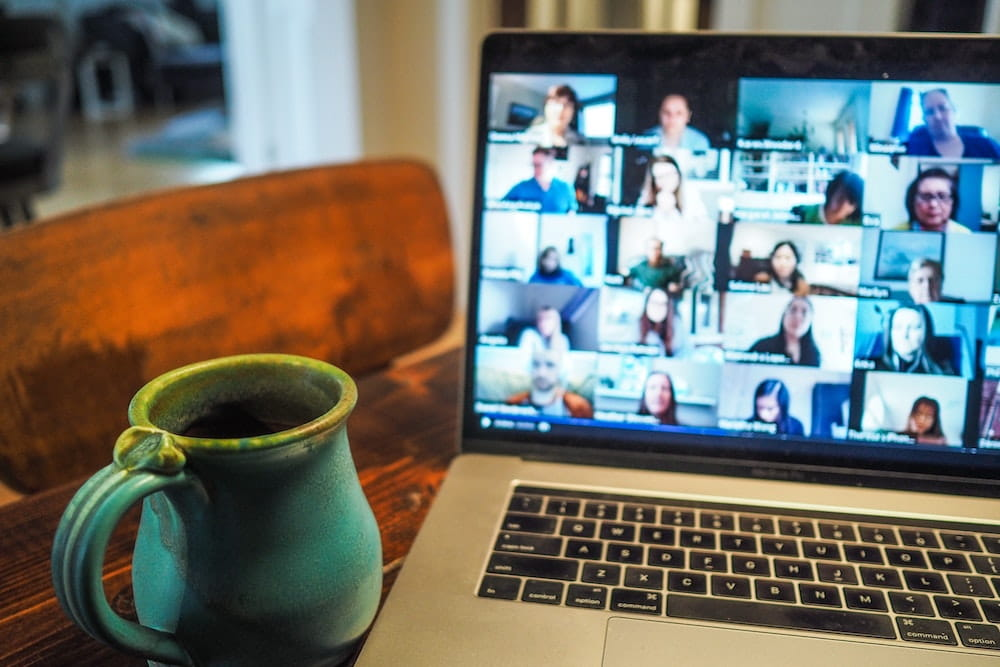 Coffee mug on table next to computer with a zoom meeting on screen